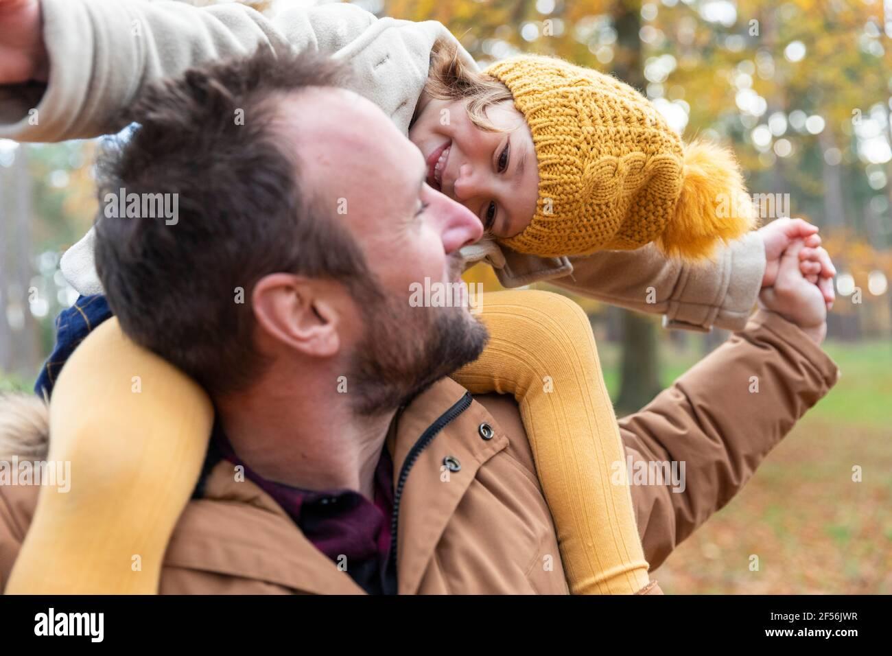 Fille souriante jouant tout en étant assise sur l'épaule du père dans la forêt Banque D'Images