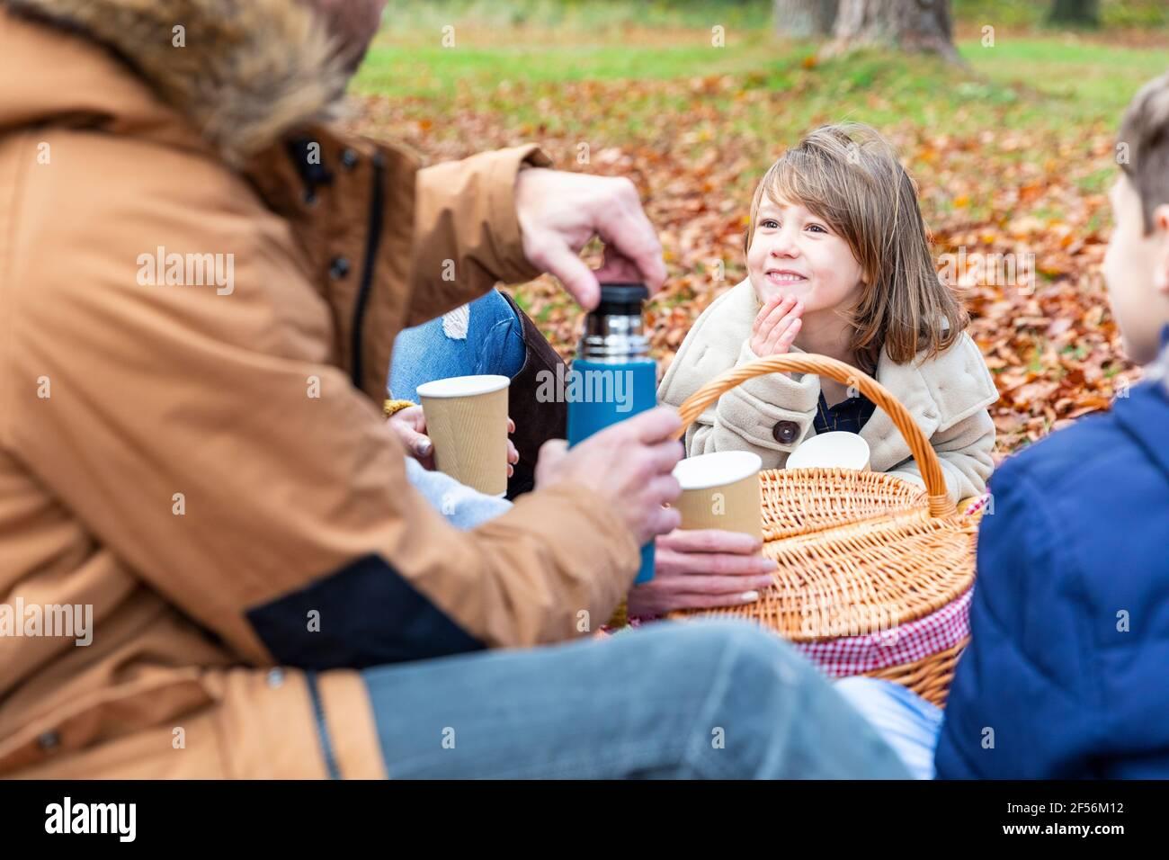 Fille souriant assis en famille dans la forêt Banque D'Images