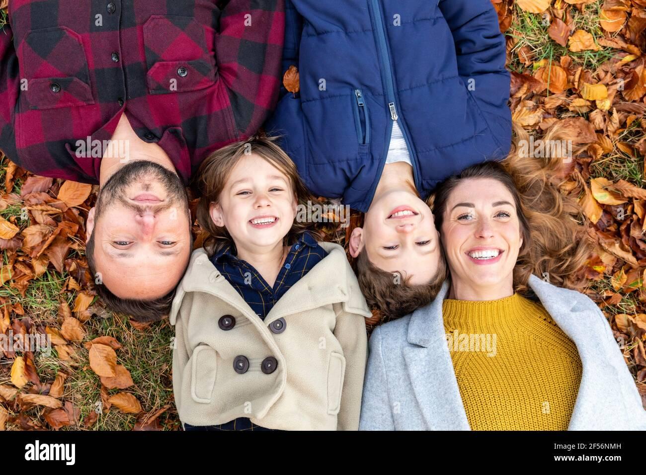 Famille souriant tout en se reposant sur la feuille tombée dans la forêt pendant automne Banque D'Images