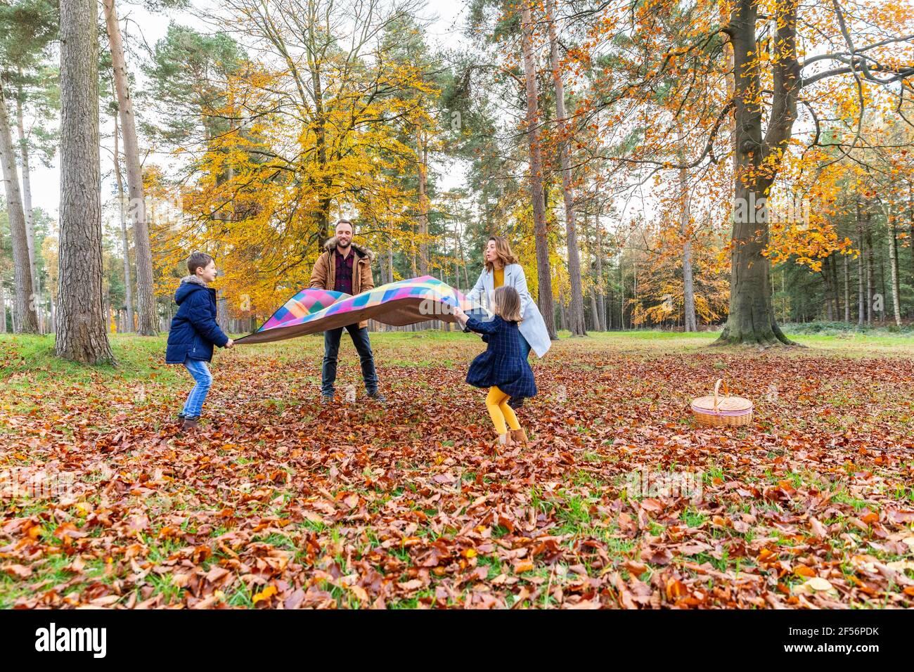 Famille tenant une couverture en se tenant dans la forêt pendant l'automne Banque D'Images
