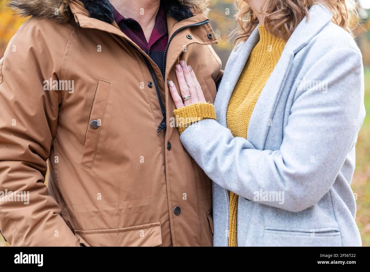 Couple portant une veste debout ensemble en forêt Banque D'Images