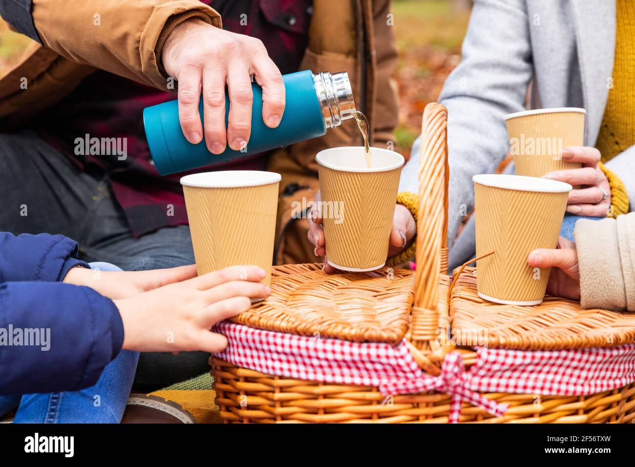 Le père verse du café dans une tasse tout en étant assis avec sa famille forêt Banque D'Images
