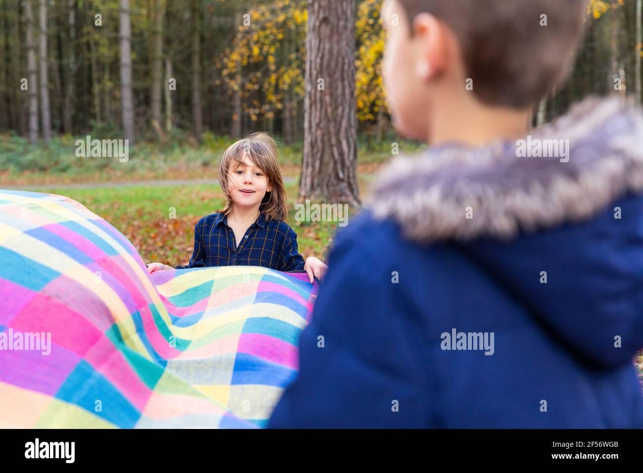 Jolie couverture de holing de fille tout en faisant la préparation de pique-nique avec frère en forêt Banque D'Images