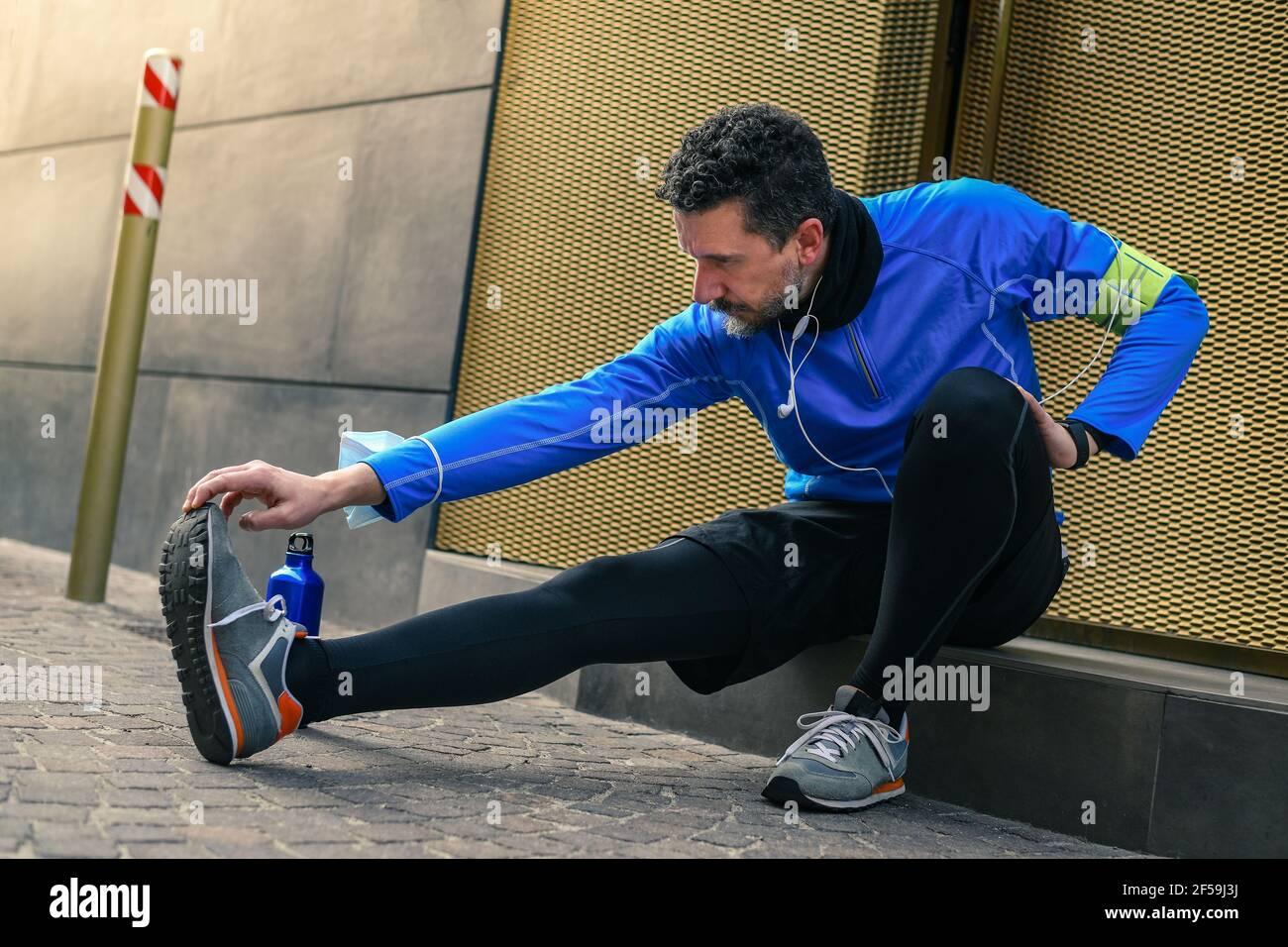 Homme s'étirant et écoutant de la musique après l'entraînement. Homme se reposant pendant le jogging de la ville. Coureur avec téléphone mobile connecté à une montre intelligente Banque D'Images