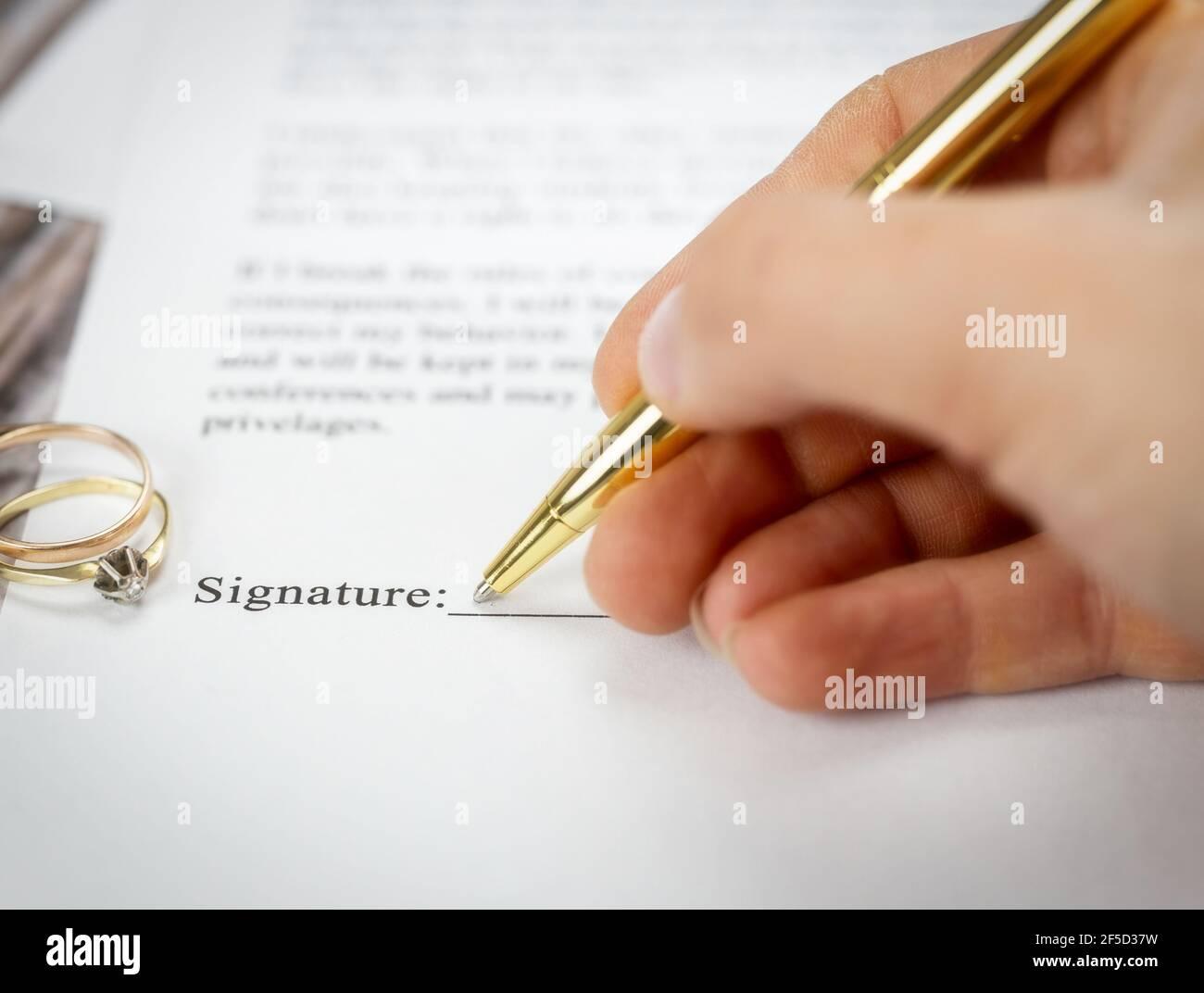 Contrat de mariage avec deux anneaux de mariage d'or et stylo d'or, accord prénuptial, macro gros plan, signer avec la signature, document, concept d'accord Banque D'Images