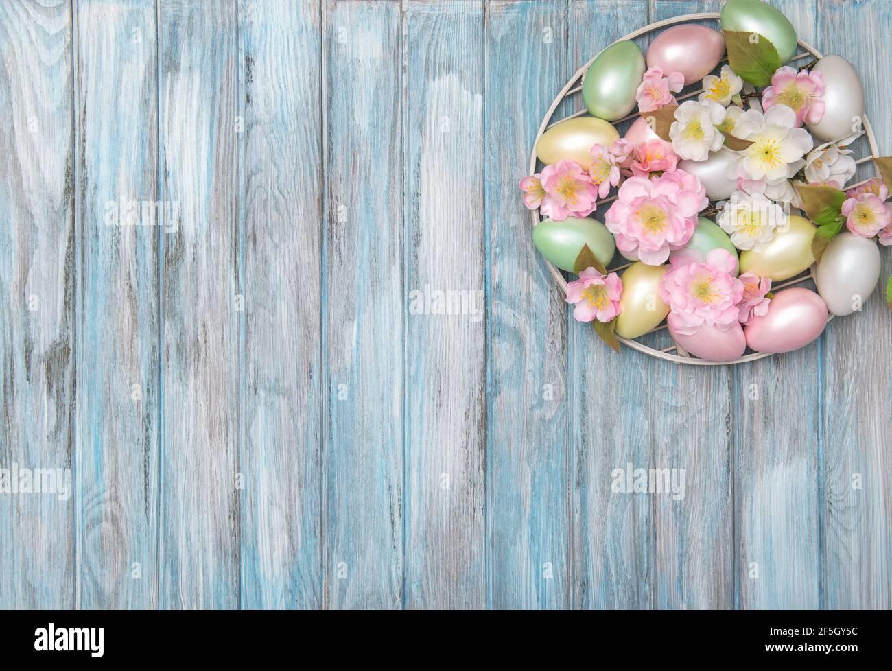 Œufs de Pâques avec décoration florale sur fond bleu en bois Banque D'Images