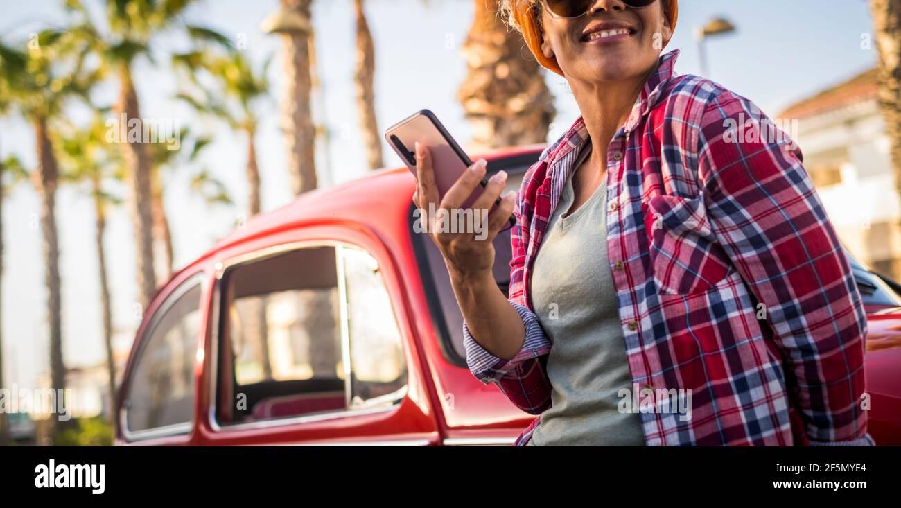 Les couleurs vintage filtrent le vieux style de film beau portrait de femme en utilisant téléphone à l'extérieur de la voiture rouge pour profiter de la journée et du mode de vie de voyage - les gens branchés et su Banque D'Images