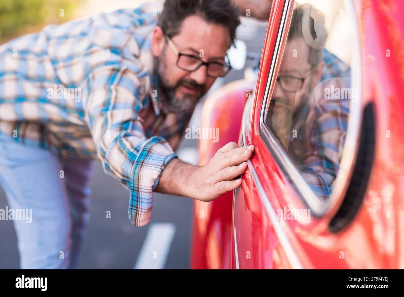 L'homme de taille basse barbu adulte vérifie le vernis de son beau voiture extérieure - les gens et le transport automobile amour et soin concept - le conducteur regarde Banque D'Images
