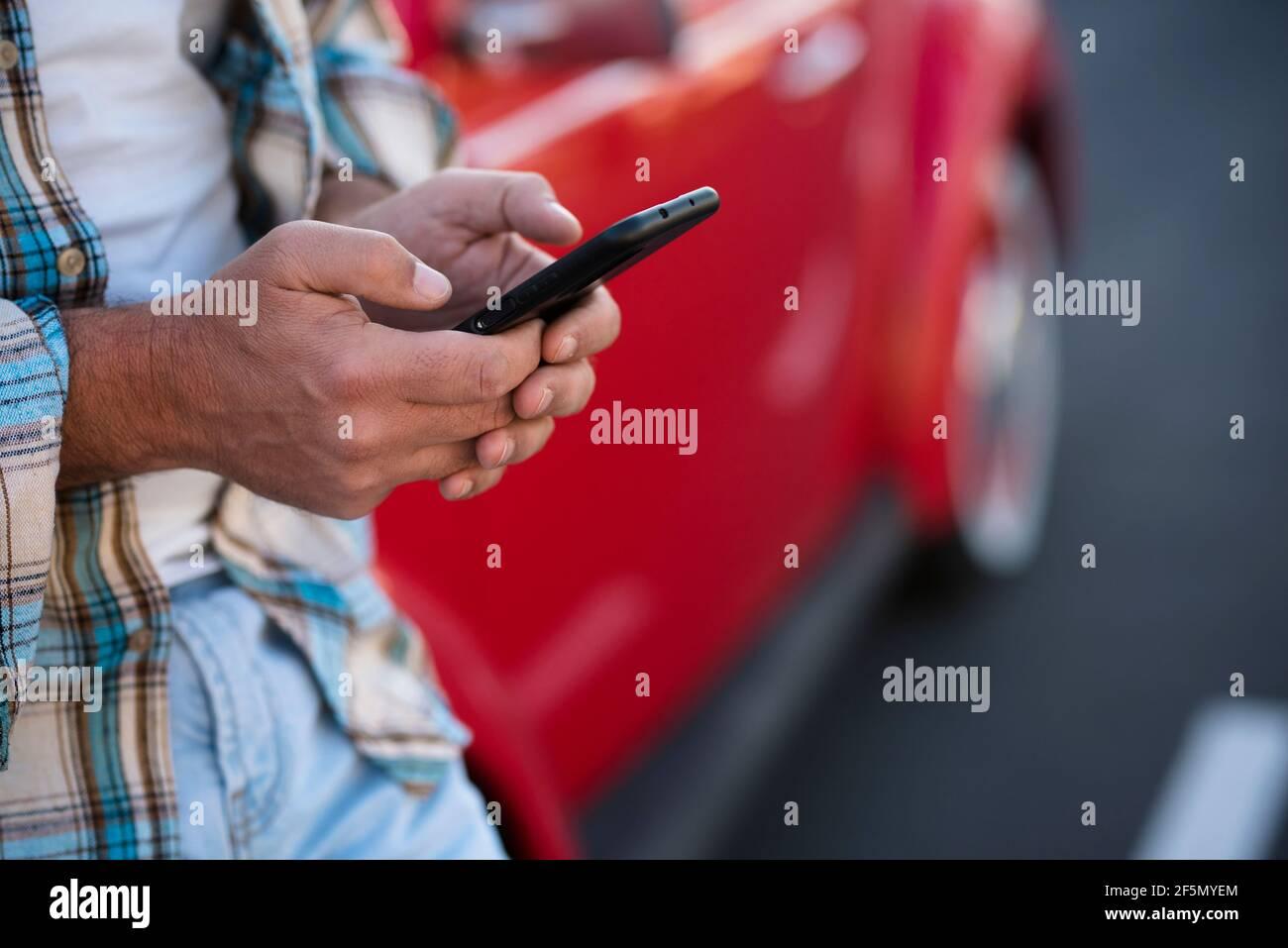 Gros plan sur un homme utilisant un téléphone à l'extérieur - personnes méconnaissables avec un smartphone cellulaire pour discuter ou envoyer des sms avec la voiture en arrière-plan - style de vie moderne avec Banque D'Images