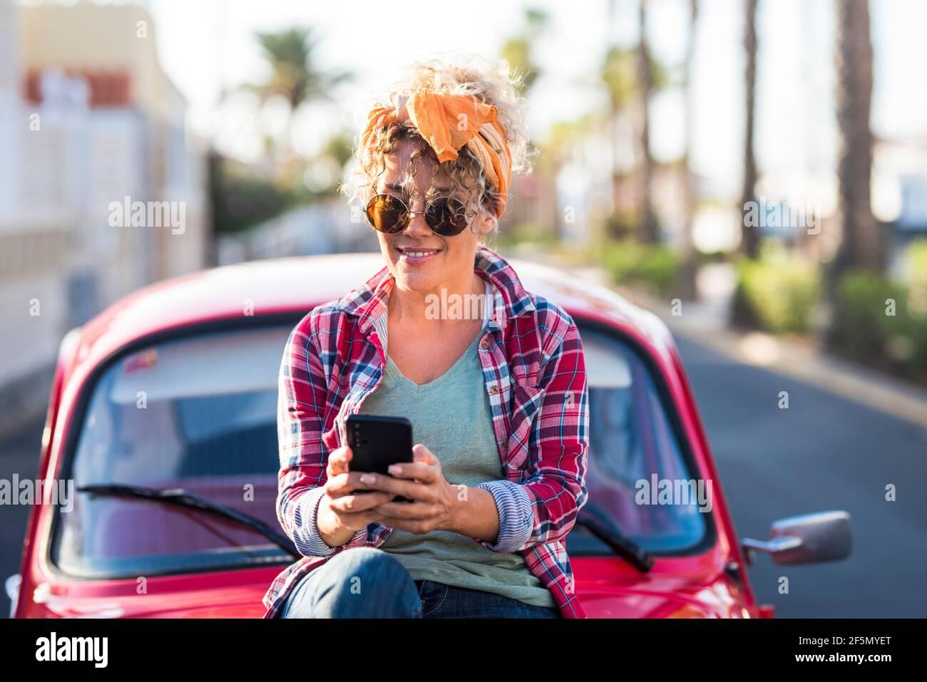 Jeune femme tendance, adulte, femme de race blanche, utilise une connexion téléphonique moderne extérieur près de sa jolie voiture rouge en voyage et indépendant style de vie - concept de Banque D'Images