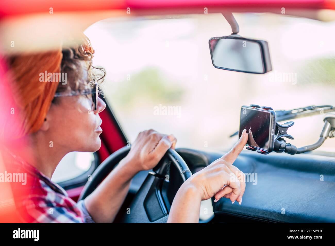 Les femmes utilisent le navigateur de cartes cellulaires par satellite à l'intérieur la voiture pour voyager et arriver destinations - femme et la technologie nav pour conduire et en Banque D'Images