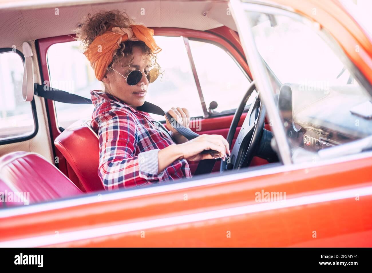 Femme tenant la ceinture de sécurité à l'intérieur de la voiture vue de extérieur - concept d'assurance et de chauffeur de femme - jeune jeune femme tendance aime voyager Banque D'Images