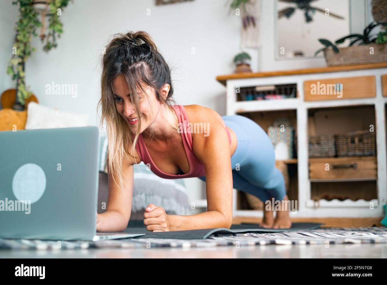 Jeune femme s'exerçant à la maison faisant des push-up et regardant sur son ordinateur portable personnel pour apprendre ou enseigner l'entraînement - le créateur de contenu d'affaires libre il Banque D'Images