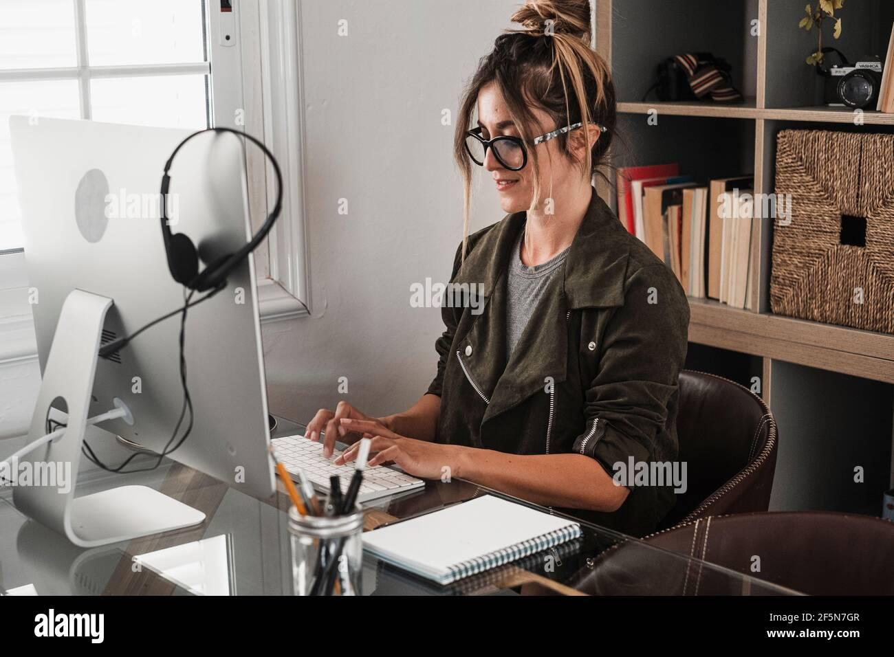 Une jeune femme d'affaires écrit sur un ordinateur portable à la maison dans l'intelligence travail de bureau travail activité de travail - concept de style de vie des travailleurs à distance avec une jolie pe femelle Banque D'Images
