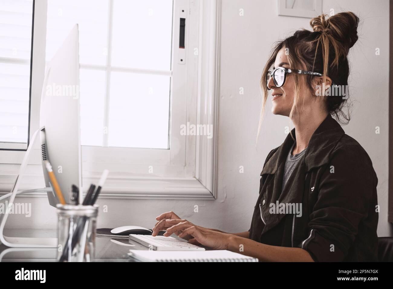 Bonne jeune femme adulte dans la vidéoconférence à la maison dans le travail intelligent, libre alternative au mode de vie de travail de bureau - joli les femmes reçoivent des nouvelles sur Banque D'Images