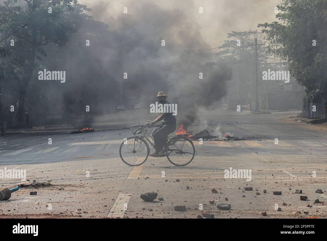Un cycliste passe devant des pneus en feu dans la rue lors d'une manifestation contre le coup d'État militaire.la police et les militaires du Myanmar (tatmadow) ont attaqué les manifestants avec des balles en caoutchouc, des munitions réelles, des gaz lacrymogènes et des bombes lacrymogènes en réponse aux manifestants anti-coup d'État militaire de samedi, tuant plus de 90 personnes et en blessant beaucoup d'autres. Au moins 300 personnes ont été tuées au Myanmar depuis le coup d'État du 1er février, a déclaré un responsable des droits de l'homme de l'ONU. L'armée du Myanmar a détenu le conseiller d'État du Myanmar Aung San Suu Kyi le 01 février 2021 et a déclaré l'état d'urgence tout en prenant le pouvoir Banque D'Images