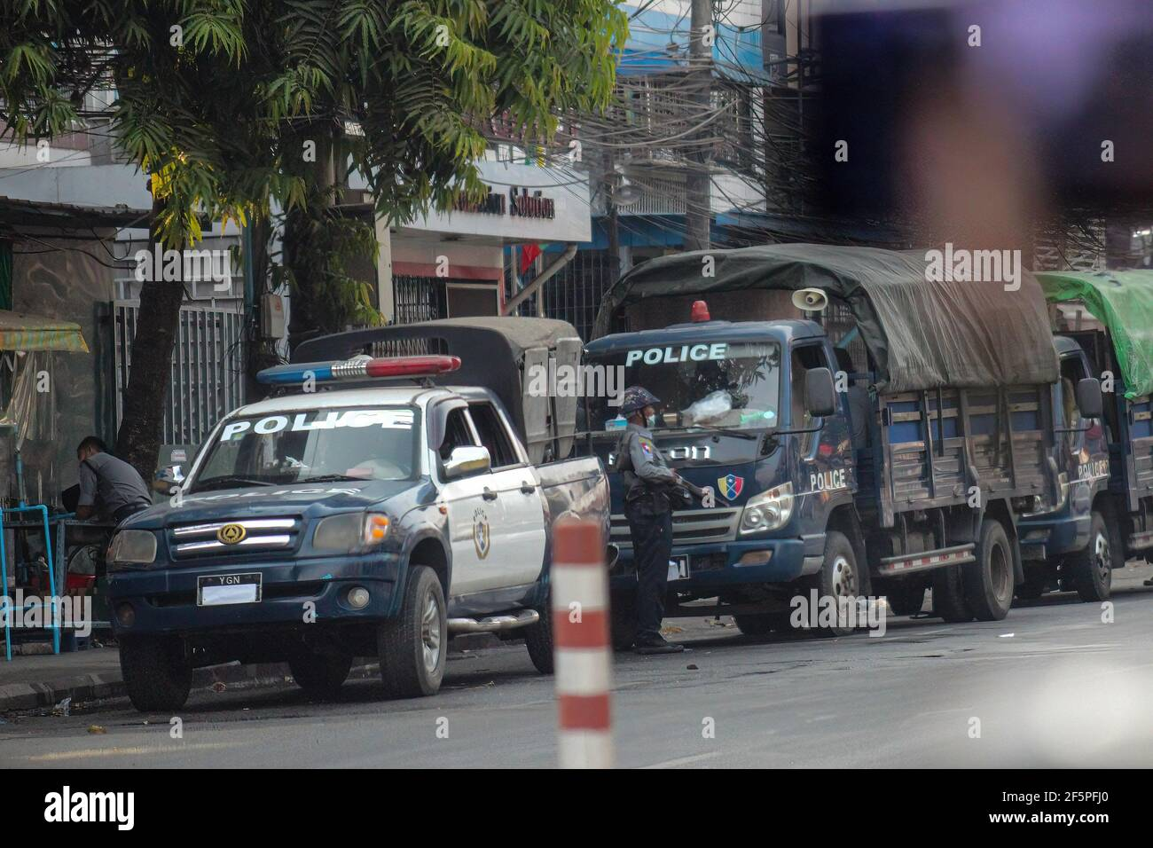 Des camions de police sont stationnés dans la rue lors d'une manifestation contre le coup d'État militaire.la police et les militaires du Myanmar (tatmadow) ont attaqué les manifestants avec des balles en caoutchouc, des munitions réelles, des gaz lacrymogènes et des bombes lacrymogènes en réponse aux manifestants anti-coup d'État militaire de samedi, tuant plus de 90 personnes et en blessant beaucoup d'autres. Au moins 300 personnes ont été tuées au Myanmar depuis le coup d'État du 1er février, a déclaré un responsable des droits de l'homme de l'ONU. L'armée du Myanmar a détenu le conseiller d'État du Myanmar Aung San Suu Kyi le 01 février 2021 et a déclaré l'état d'urgence tout en prenant le pouvoir Banque D'Images