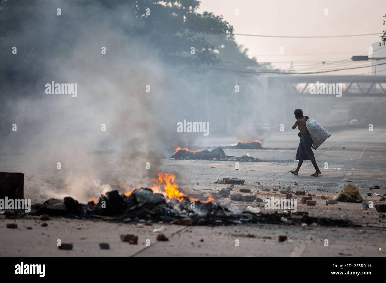Yangon, Myanmar. 27 mars 2021. Un préparateur de bouteilles passant par les pneus en feu pendant la démonstration. L'armée birmane attaque les manifestants avec des balles en caoutchouc, des munitions réelles, des gaz lacrymogènes et des bombes sonores en réponse. Le nombre de morts pour aujourd'hui est de 144 et le plus élevé depuis le coup d'État militaire du 1er février. (Photo de Theint mon SOE/SOPA Images/Sipa USA) Credit: SIPA USA/Alay Live News Banque D'Images