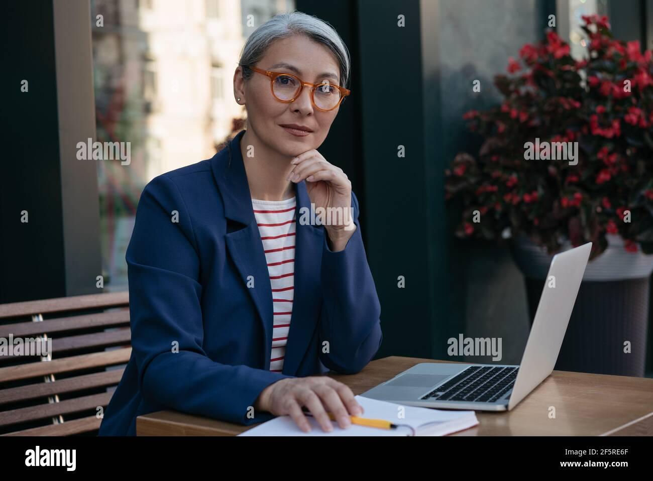 Femme d'affaires pensive et mûre regardant la caméra, assise sur le lieu de travail. Beau travailleur indépendant d'âge moyen, utilisant un ordinateur portable, projet de planification Banque D'Images