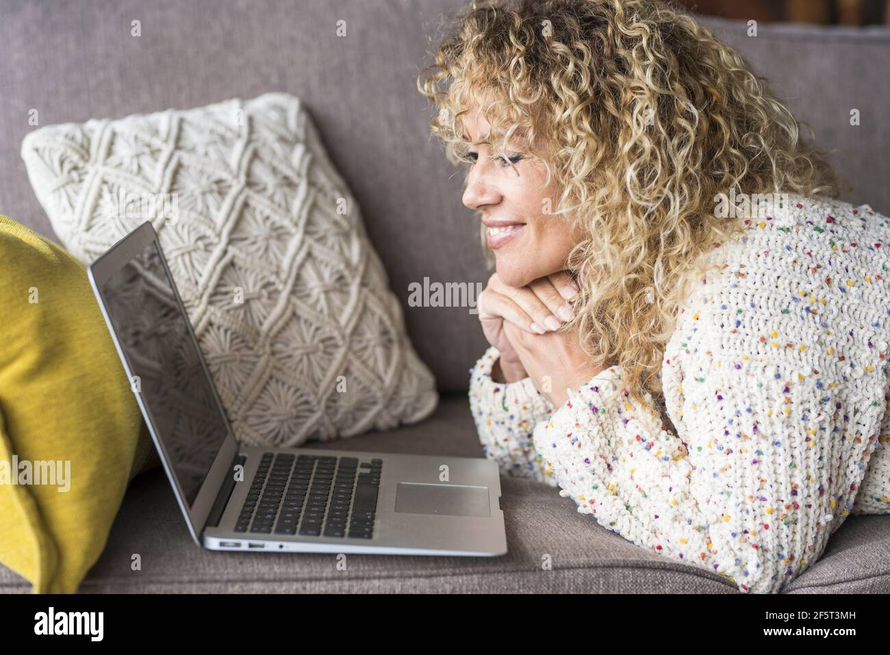Une femme adulte s'est couché à la maison et se détend avec ordinateur portable : les utilisateurs et les appareils à la maison la vie et le séjour confortables - caucasien f Banque D'Images