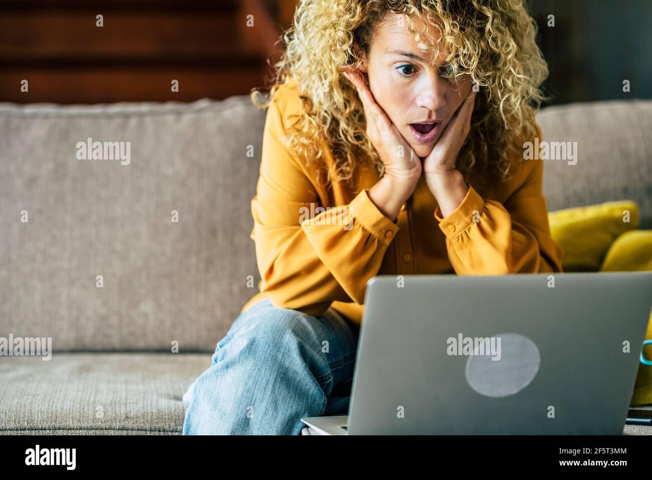 Une femme souriante assise à la maison sur le canapé lisant un message en regardant l'écran de l'appareil à l'aide d'un ordinateur. Une femme excitée se sent satisfaite de l'émotion positive Banque D'Images