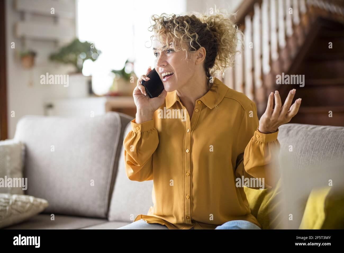 Une femme adulte heureuse à la maison dans le téléphone appelant sourire et profitez d'un moment de loisirs à l'intérieur assis sur le canapé style de vie décontracté - âge moyen élégant pe Banque D'Images