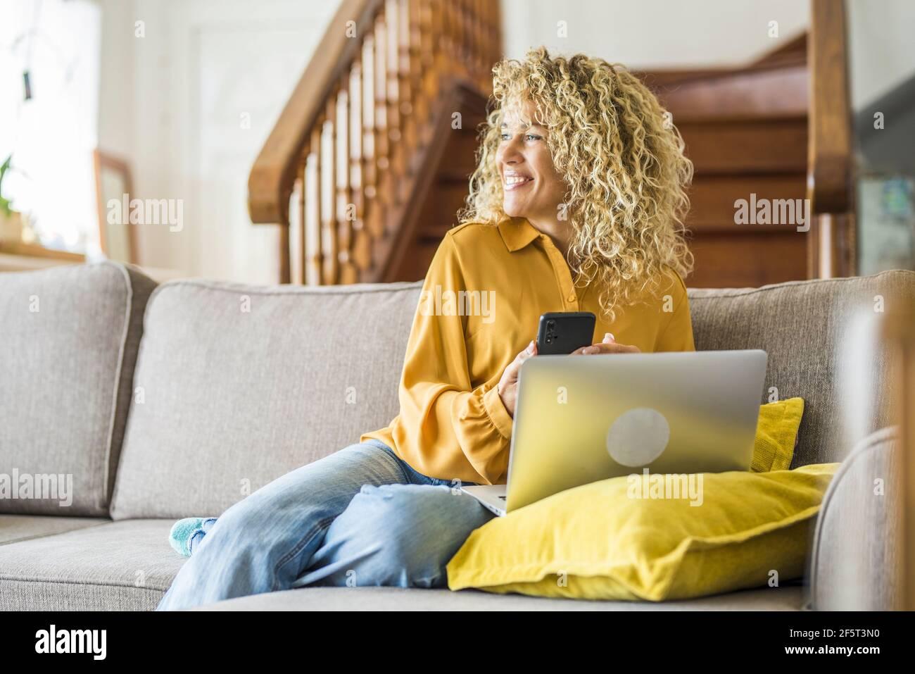 Souriante adulte jeune femme s'assoir se détendre sur le canapé en utilisant l'ordinateur portable moderne de navigation Internet sans fil illimité, heureux jeunes indépendants travail sur ordinateur Banque D'Images