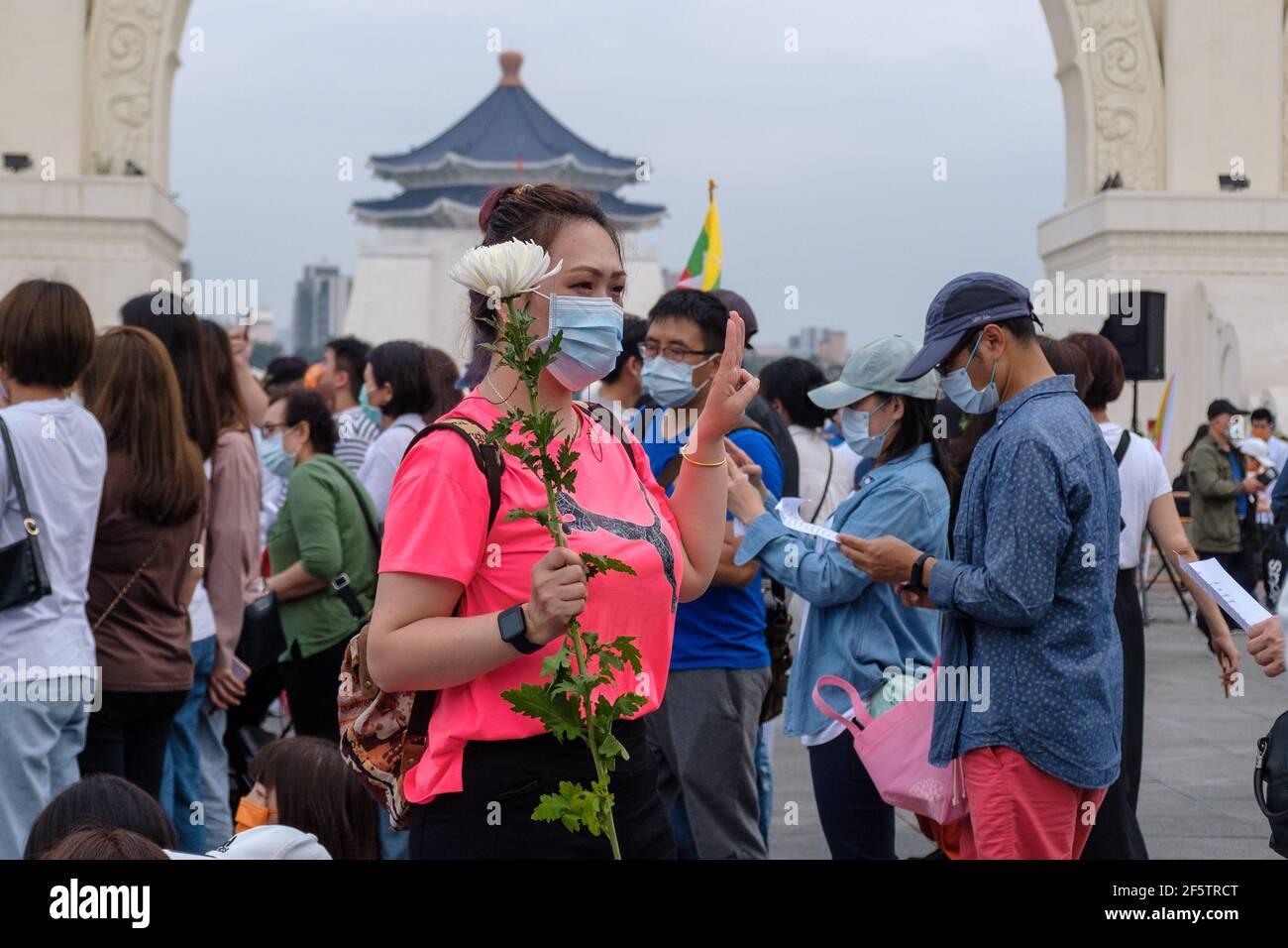 Un manifestant salue à trois doigts tout en tenant une fleur pendant la manifestation.birman vivant à Taiwan avec les communautés locales rassemblées sur la place de la liberté pour appeler à la fin du coup d'État militaire au Myanmar. La police et les militaires du Myanmar (tatmadow) ont attaqué les manifestants avec des balles en caoutchouc, des munitions réelles, des gaz lacrymogènes et des bombes lacrymogènes en réponse aux manifestants anti-coup d'État militaire qui ont tué samedi au Myanmar plus de 100 personnes et en ont blessé beaucoup d'autres. Au moins 300 personnes ont été tuées au Myanmar depuis le coup d'État du 1er février, a déclaré un responsable des droits de l'homme de l'ONU. Myanmar Banque D'Images