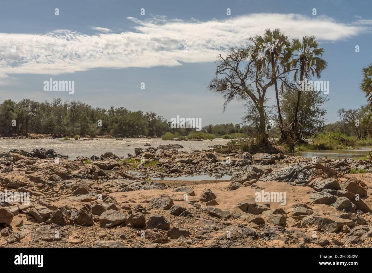 Vue sur le paysage de la rivière Kunene, la rivière frontalière entre la Namibie et l'Angola Banque D'Images