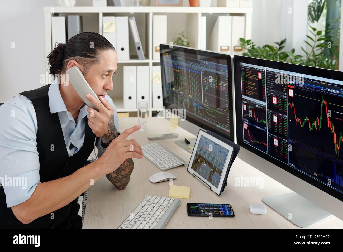 Trader professionnel vérifiant les données du marché boursier sur des écrans sur ordinateur et table numérique et passer un appel téléphonique Banque D'Images