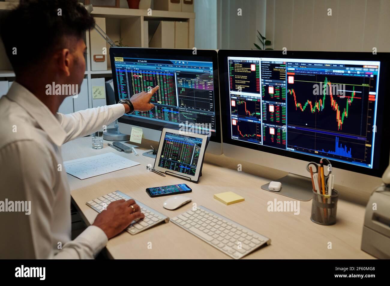 Jeune commerçant indien professionnel travaillant dans le bureau noir et le pointage sur l'écran de l'ordinateur avec des informations sur le marché boursier Banque D'Images
