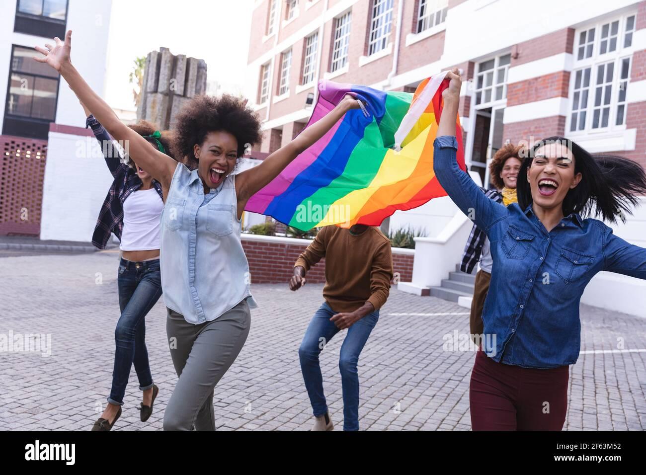 Divers hommes et femmes protestant en mars, arborant le drapeau de l'arc-en-ciel, applaudissent avec les armes levées Banque D'Images