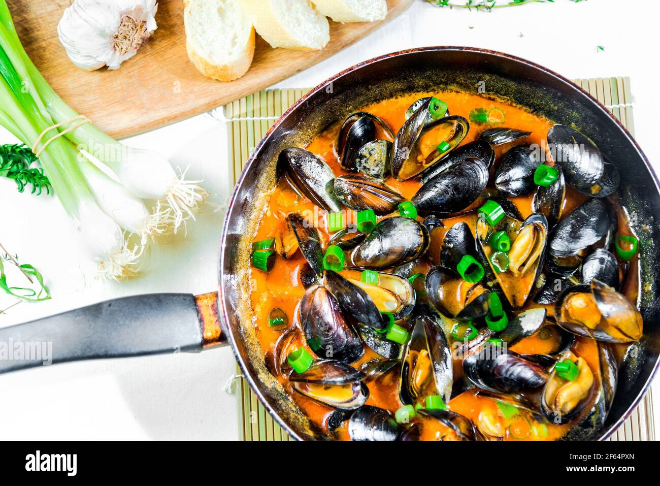 Délicieux moules de fruits de mer avec sauce rouge et oignons verts une casserole Banque D'Images