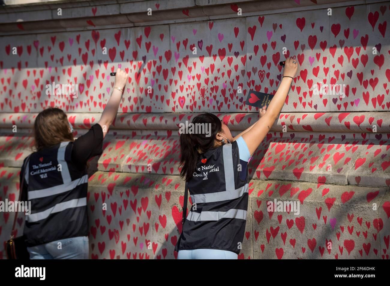 Londres, Royaume-Uni. 30 mars 2021. Les volontaires tirent les coeurs sur un mur à Lambeth, près de la Tamise, chaque coeur représentant quelqu'un qui est décédé pendant la pandémie de coronavirus au Royaume-Uni. Appelé le mur commémoratif national Covid, il a été créé par les familles bereaved Covid-19 pour la justice et s'étendra sur un demi-mile au moment où il sera terminé. Crédit : Stephen Chung/Alay Live News Banque D'Images