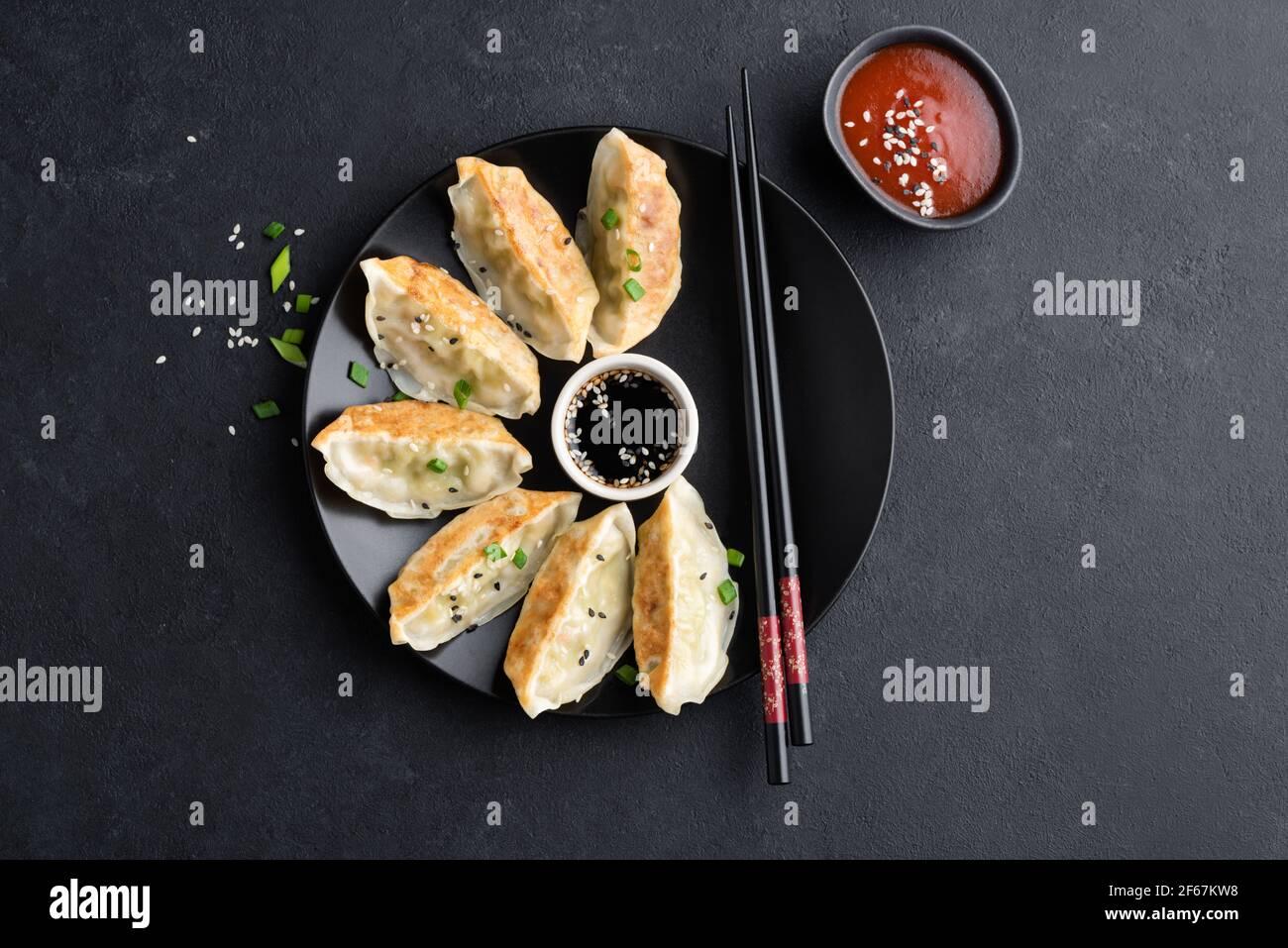Nourriture asiatique Gyoza ou Jiaozi beignets servis avec sauce soja, sauce crevettes et graines de sésame sur fond de béton noir, vue du dessus Banque D'Images
