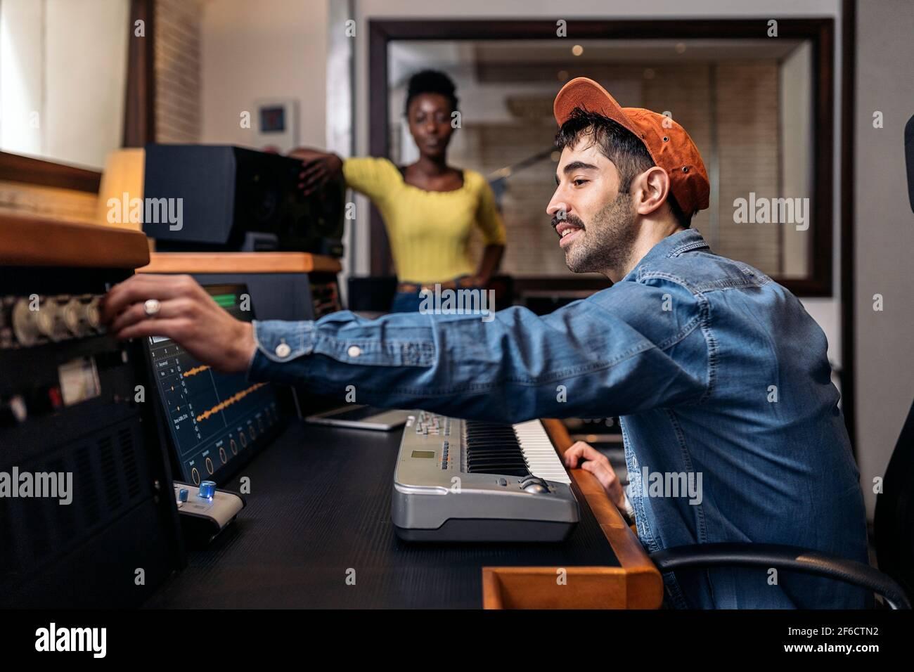 Photo de la bonne femme noire en studio de musique et producteur de sexe masculin utilisant un clavier de piano électronique. Banque D'Images