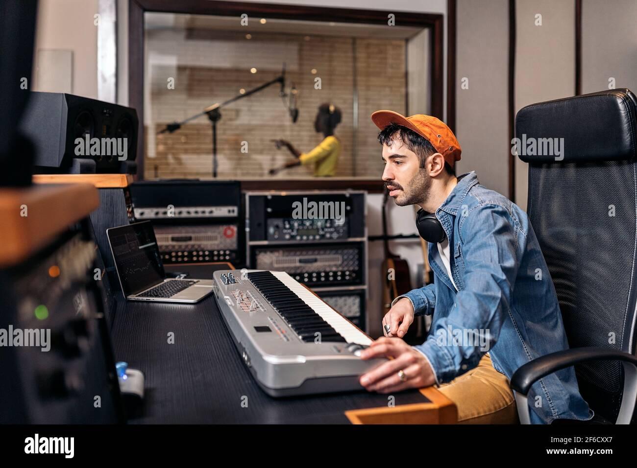 Photo d'un producteur de musique masculin travaillant avec un chanteur noir dans un studio de musique cool. Banque D'Images