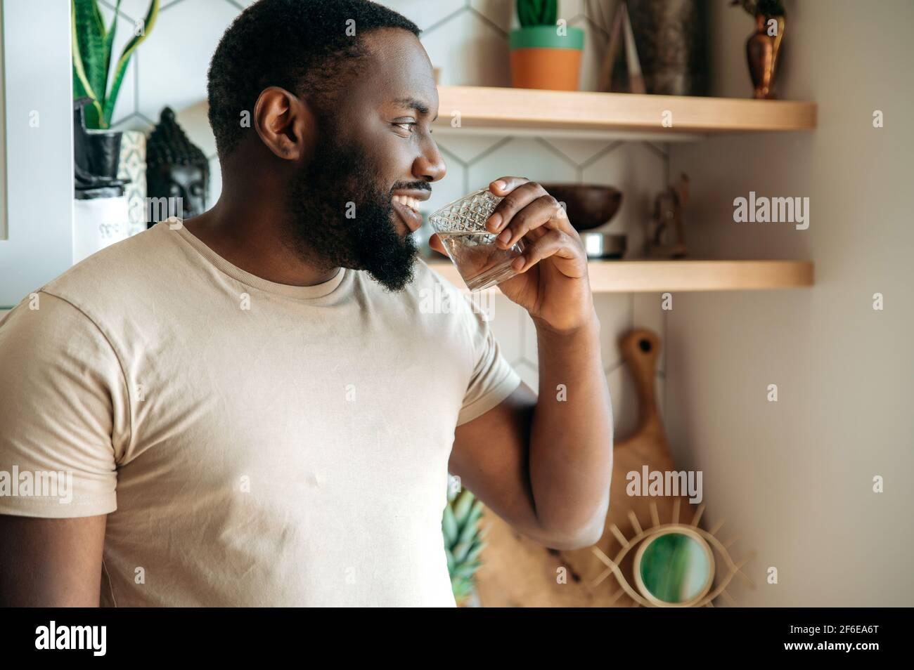Afro-américain attrayant homme de boire une eau pure, suivre un mode de vie sain. Un beau gars se sent assoiffé, boit quotidiennement une quantité de liquide pur, debout à la cuisine, concept de soins de santé Banque D'Images