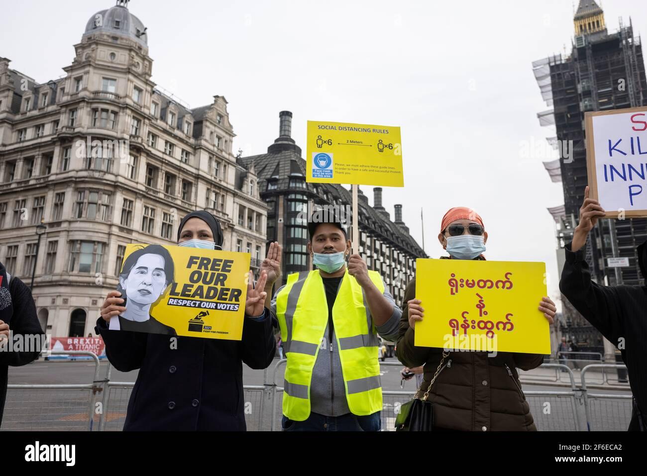 Londres, Royaume-Uni. 31 mars 2021. Des manifestants avec des pancartes et faisant le salut de trois doigts de la résistance sur la place du Parlement. Les manifestants se sont rassemblés sur la place du Parlement - portant un masque facial et observant les distances sociales - avant de marcher vers l'ambassade chinoise en solidarité avec le peuple du Myanmar contre le coup d'État militaire et les meurtres de civils par l'État. Des discours ont été prononcés à l'extérieur de l'ambassade. Depuis le début du coup d'État militaire le 1er février, plus de 520 personnes ont été tuées au Myanmar par les forces de sécurité. Samedi dernier a été le jour le plus violent où plus de 100 personnes étaient kil Banque D'Images