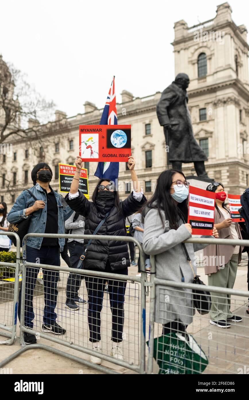 Londres, Royaume-Uni. 31 mars 2021. Des manifestants dressent des pancartes près de la statue de Winston Churchill sur la place du Parlement. Les manifestants se sont rassemblés sur la place du Parlement - portant un masque facial et observant les distances sociales - avant de marcher vers l'ambassade chinoise en solidarité avec le peuple du Myanmar contre le coup d'État militaire et les meurtres de civils par l'État. Des discours ont été prononcés à l'extérieur de l'ambassade. Depuis le début du coup d'État militaire le 1er février, plus de 520 personnes ont été tuées au Myanmar par les forces de sécurité. Samedi dernier a été le jour le plus violent où plus de 100 personnes ont été tuées. De la Banque D'Images