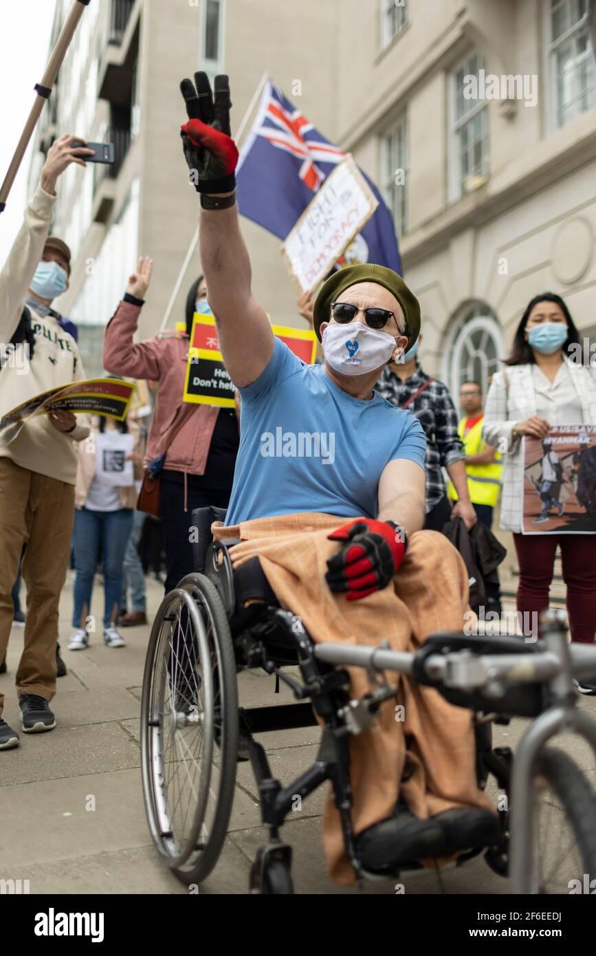 Londres, Royaume-Uni. 31 mars 2021. Un homme handicapé montre son soutien et rend hommage à trois doigts de la résistance. Les manifestants se sont rassemblés sur la place du Parlement - portant un masque facial et observant les distances sociales - avant de marcher vers l'ambassade chinoise en solidarité avec le peuple du Myanmar contre le coup d'État militaire et les meurtres de civils par l'État. Des discours ont été prononcés à l'extérieur de l'ambassade. Depuis le début du coup d'État militaire le 1er février, plus de 520 personnes ont été tuées au Myanmar par les forces de sécurité. Samedi dernier a été le jour le plus violent où plus de 100 personnes ont été tuées. Crédit : Banque D'Images