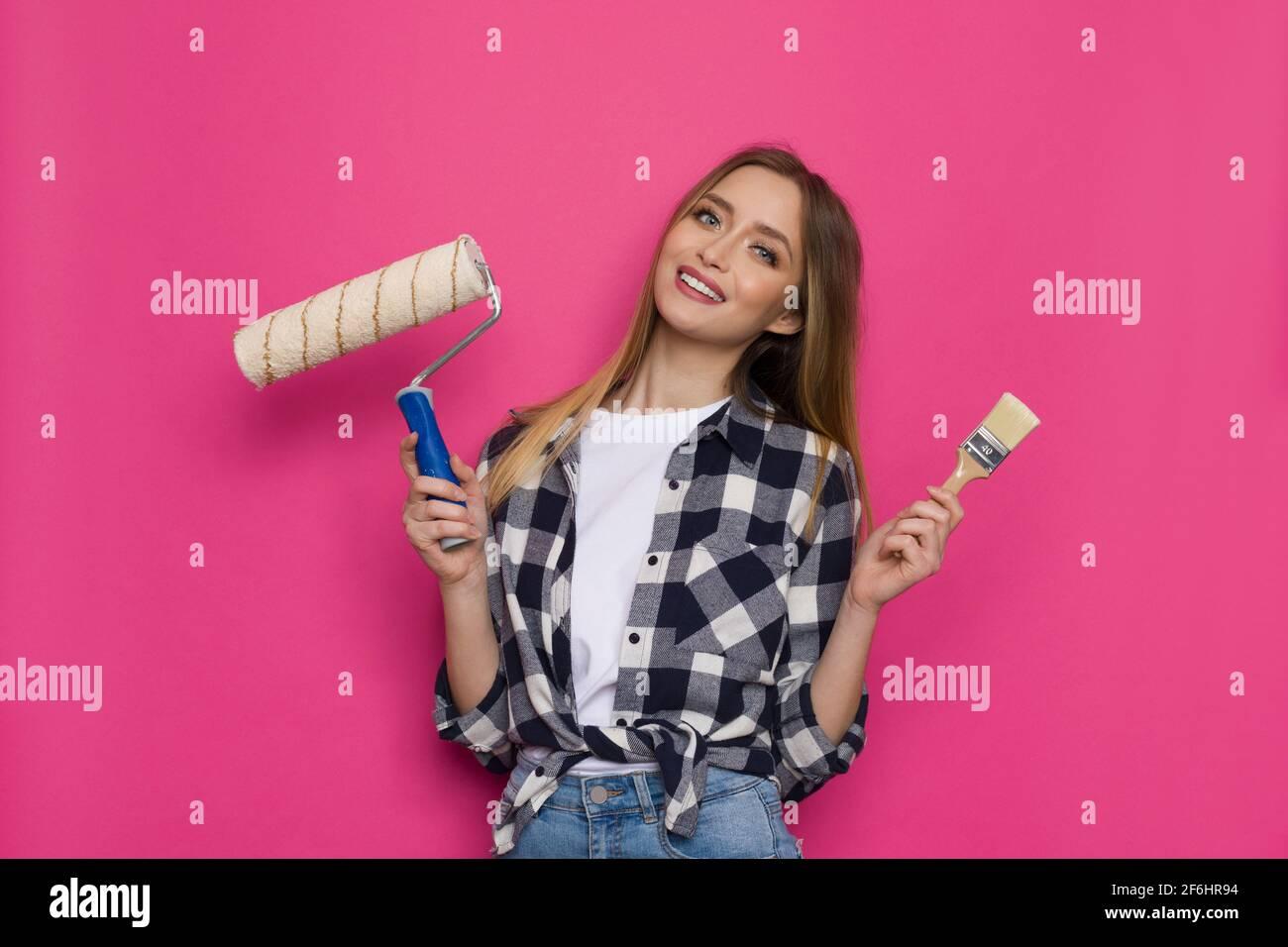 Une jeune femme souriante en chemise de bûcherons tient un pinceau et un rouleau de peinture. Vue avant. Taille haute studio tourné sur fond rose. Banque D'Images