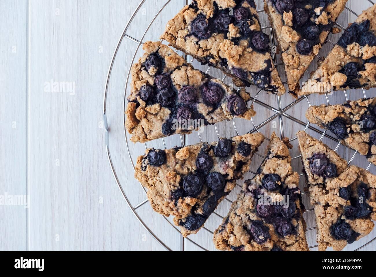 Scones aux myrtilles d'avoine fraîchement cuites sur un support de refroidissement sur fond de bois blanc, vue de dessus, plat. Pâte à base de légumes et de plantes, gros plan. Mets sucrés. Banque D'Images