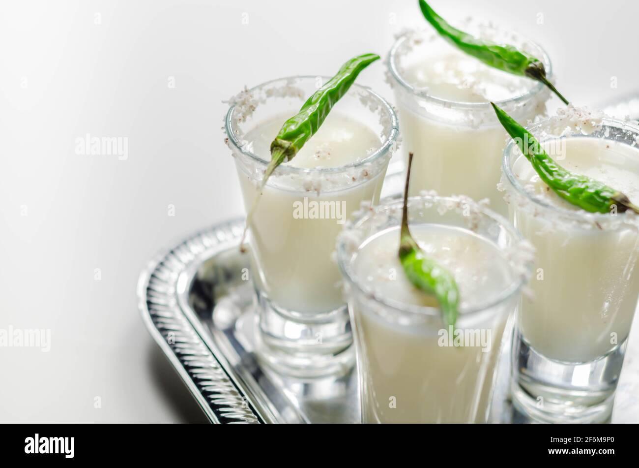 Cocktail de noix de coco en verre à boire décoré de flocons de noix de coco et de piment vert pour les yeux d'oiseaux servi sur un plateau argenté, boissons blanches Banque D'Images