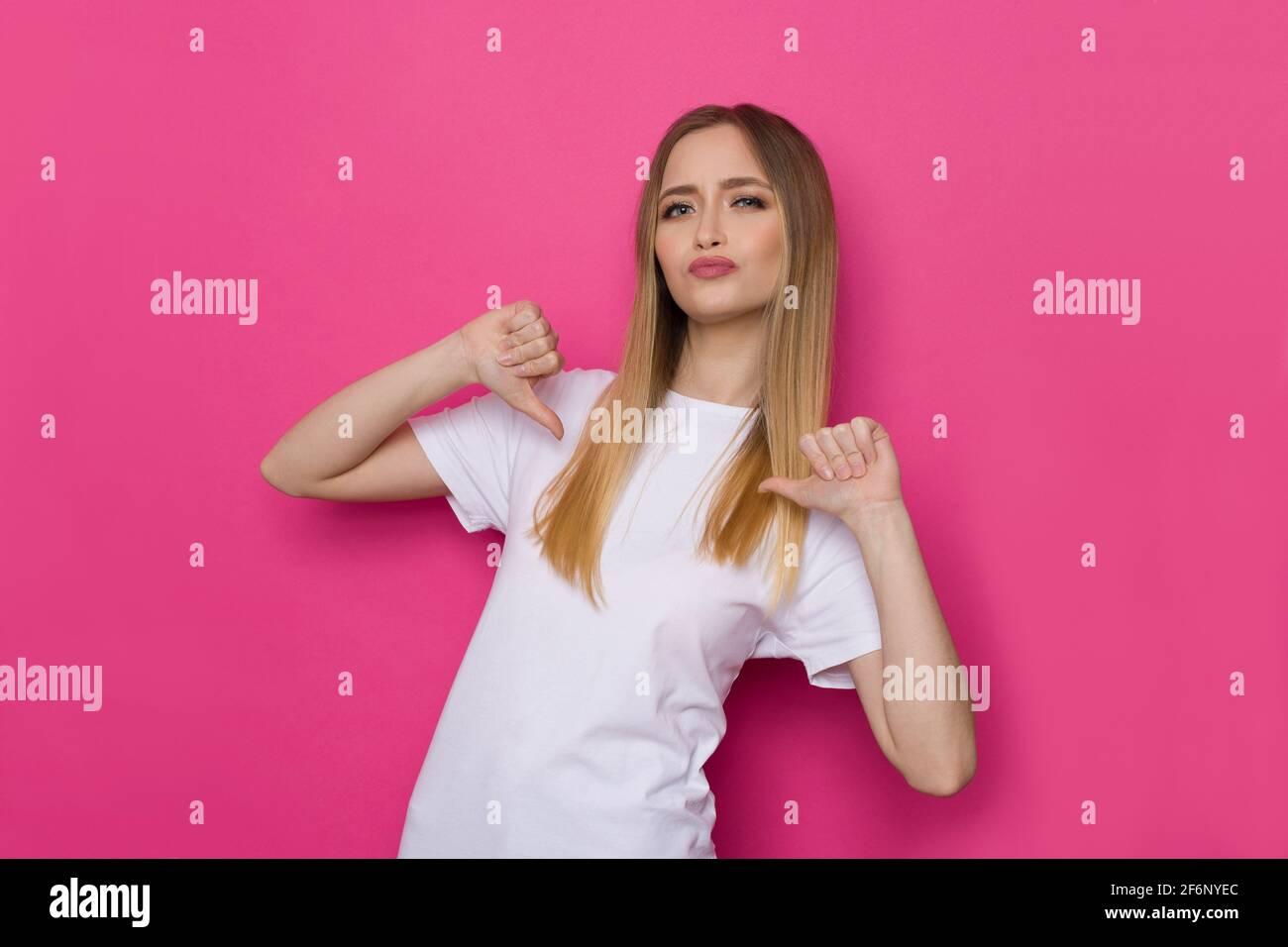 Une jeune femme confiante en chemise blanche se pointe vers elle avec les pouces. Taille haute studio tourné sur fond rose. Banque D'Images