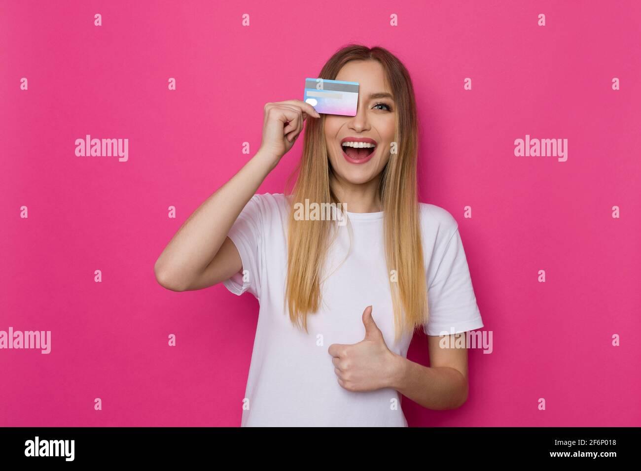 Rire jeune femme en chemise blanche couvre l'œil avec la carte de crédit et donne le pouce vers le haut. Taille haute studio tourné sur fond rose. Banque D'Images