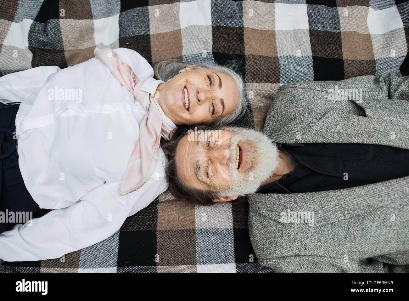 Vue de dessus d'un couple d'âge mûr caucasien allongé tête à tête sur une couverture à damier et souriant sur l'appareil photo. Bonne retraite. Amour pour les âges. Banque D'Images