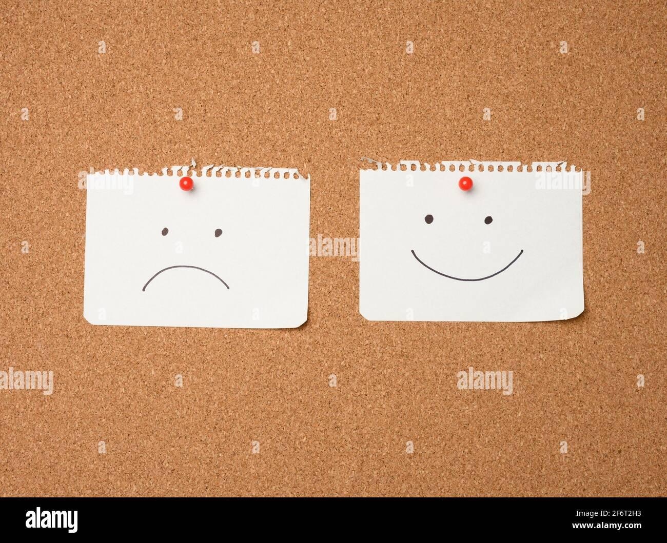 deux feuilles de papier avec un sourire et une triste émotion attachée avec un bouton sur un tableau marron, la joie et la dépression. Banque D'Images