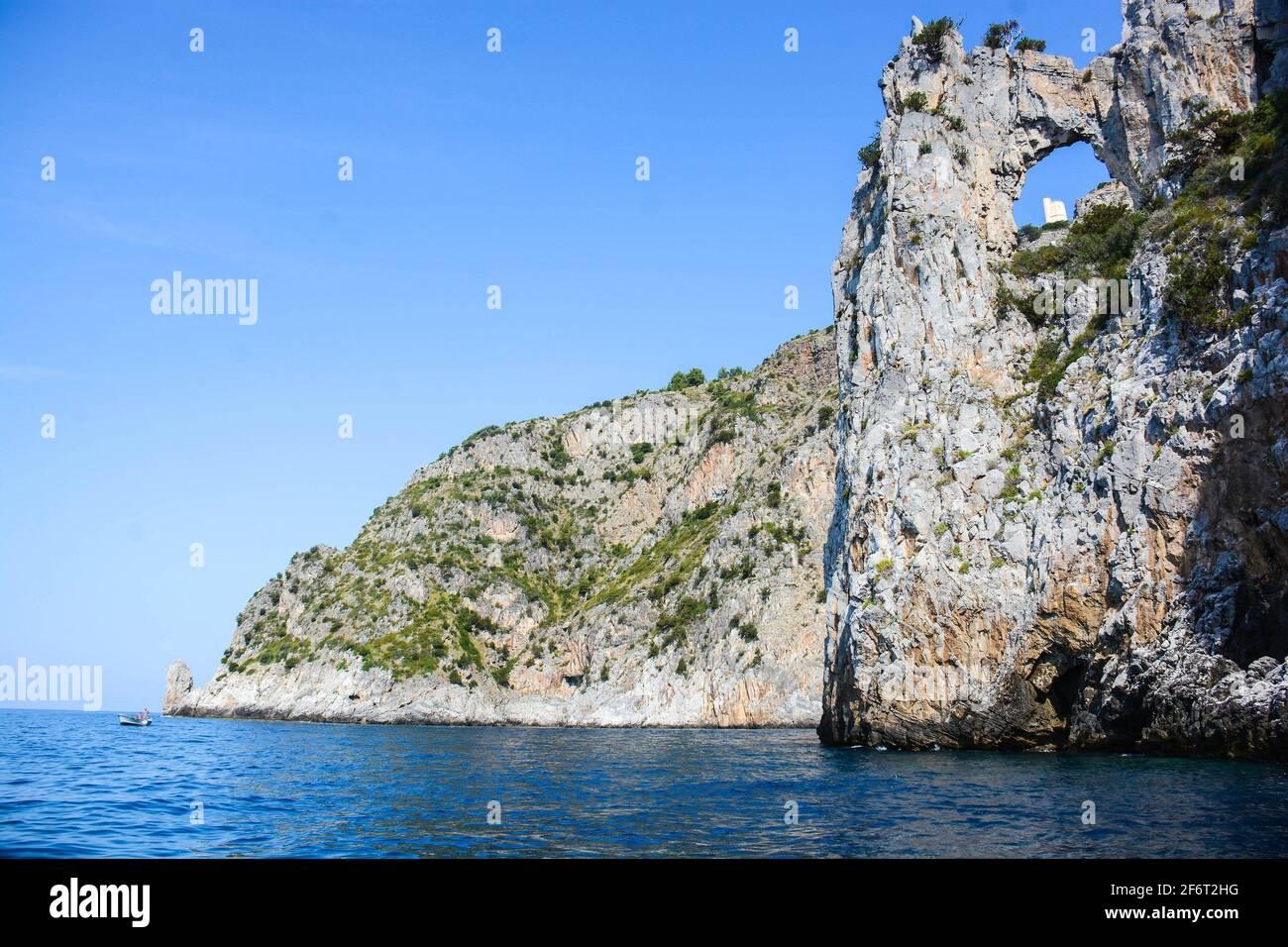 Vue sur la tour de Saracen restaurée à travers le cercle naturel de la falaise à Palinuro en Italie, visible seulement de la mer et de Capo Spartivento. Banque D'Images