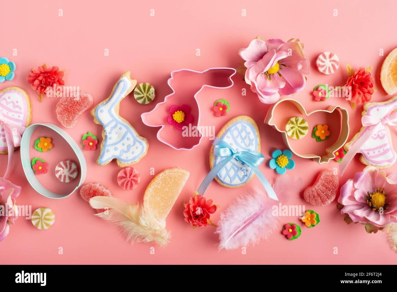 Biscuits givrés de Pâques en forme de poulet à l'œuf et de lapin, saupoudrés de sucre, bonbons, emporte-pièces sur fond rose. Maquette de pose à plat. Banque D'Images